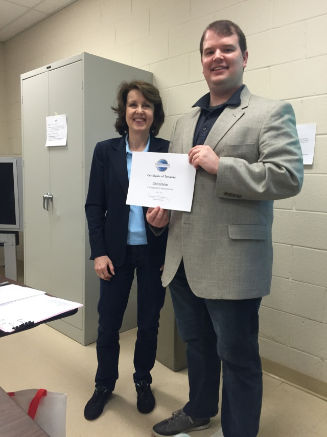 Chris receives a certificate from Margaret after completing his tenth speech.